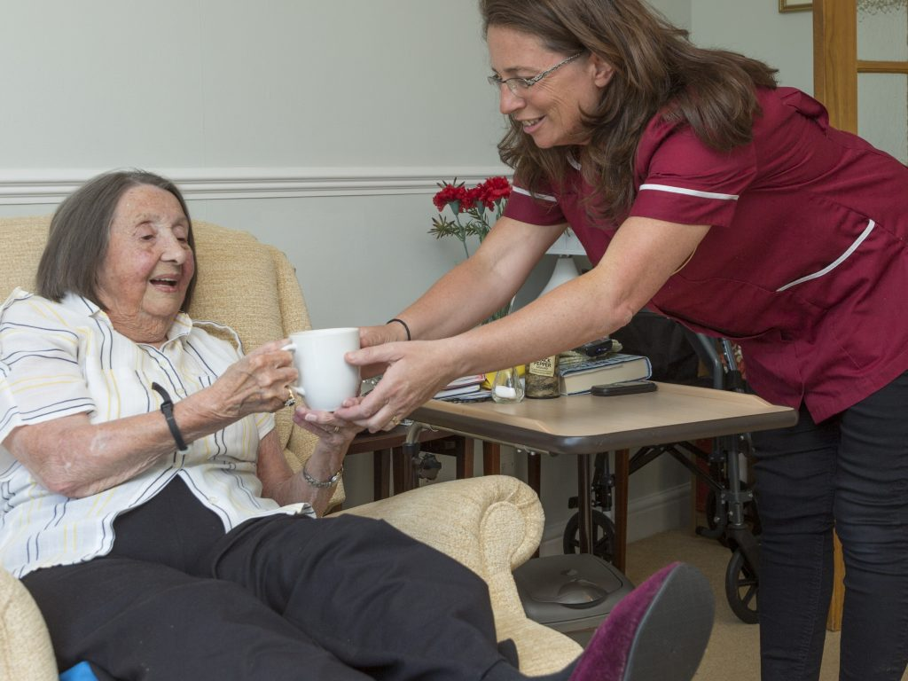 Carer serves a cup of tea to a client