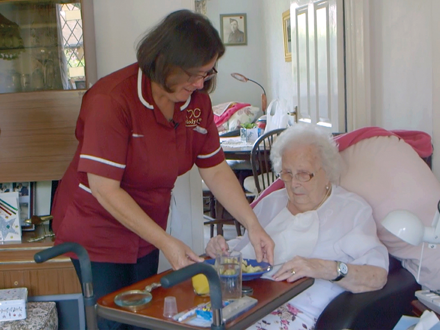 Home Care Assistant helps client with breakfast